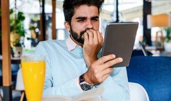 Homem reflexivo olhando para o seu tablet