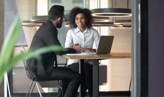 Duas pessoas (um homem e uma mulher) conversando no ambiente de trabalho