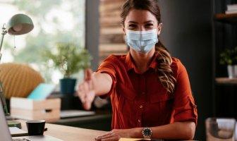 recrutadora com máscara faz um gesto de cumprimento
