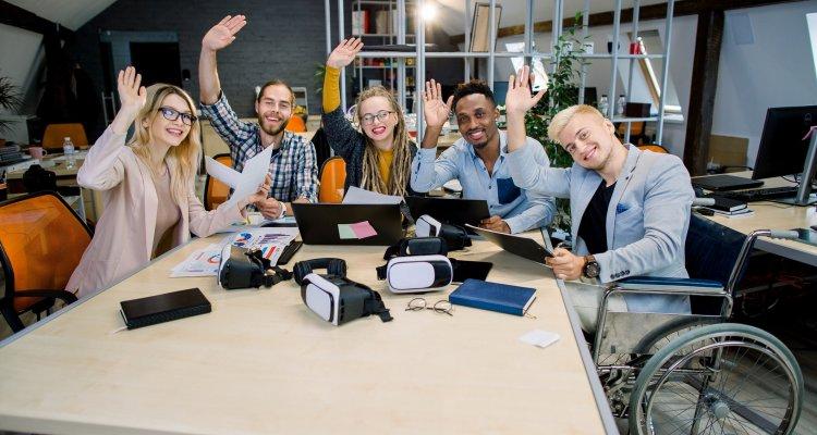 equipe de talentos diversos acenam à mão numa mesa de reunião