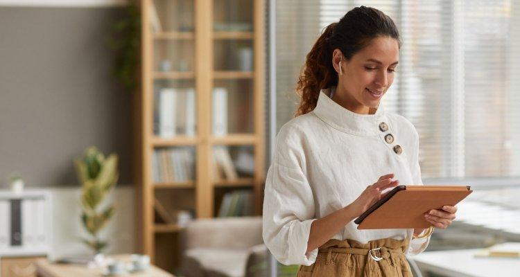 Mulher utilizando um tablet em sua casa