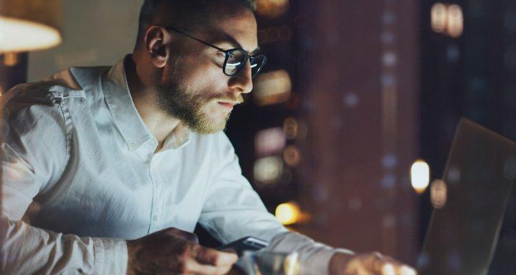 Homem olhando atenciosamente para o seu notebook durante o trabalho