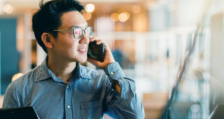 Homem no celular conversando dentro do ambiente de trabalho