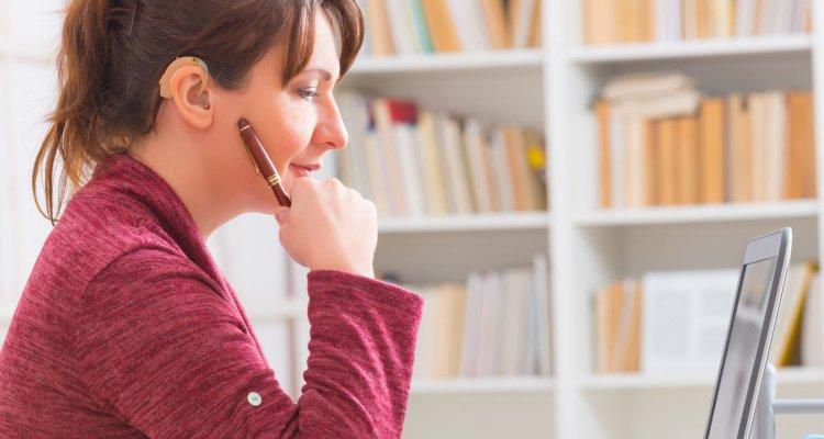 Mulher com aparelho auditivo em seu ambiente de trabalho