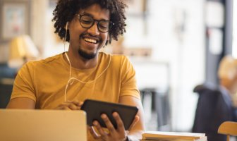 Homem jovem olhando para o seu celular sorridente
