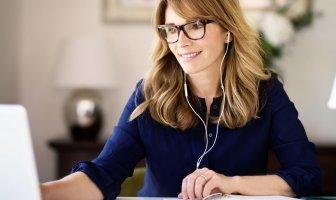 Mulher com fone de ouvido olhando para o seu notebook enquanto trabalha