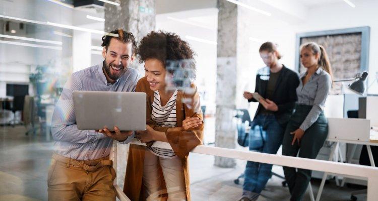 Executivos observam a tela de um notebook e dão risada, ao fundo outros jovens executivos observam a cena